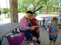A clown and 2 kids sit in a park picnic area.