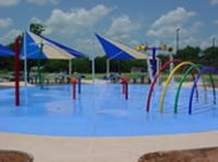 Splash park with water, tents, and water toys for kids.