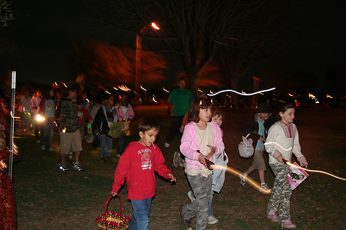 A group of kids and adults walk down the street with bags and flashlights at night.